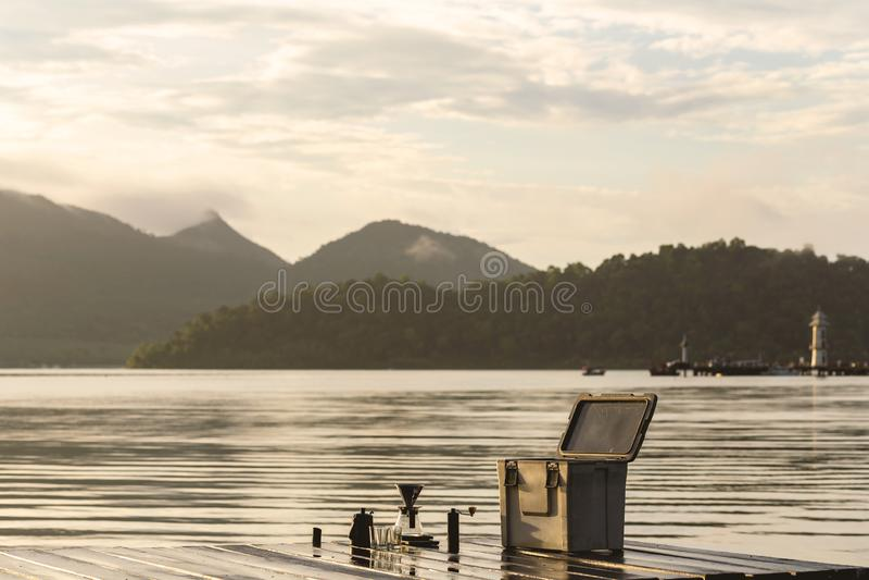 酿造在清早大气的咖啡的设备 渔夫的码头和山的背景 免版税图库摄影