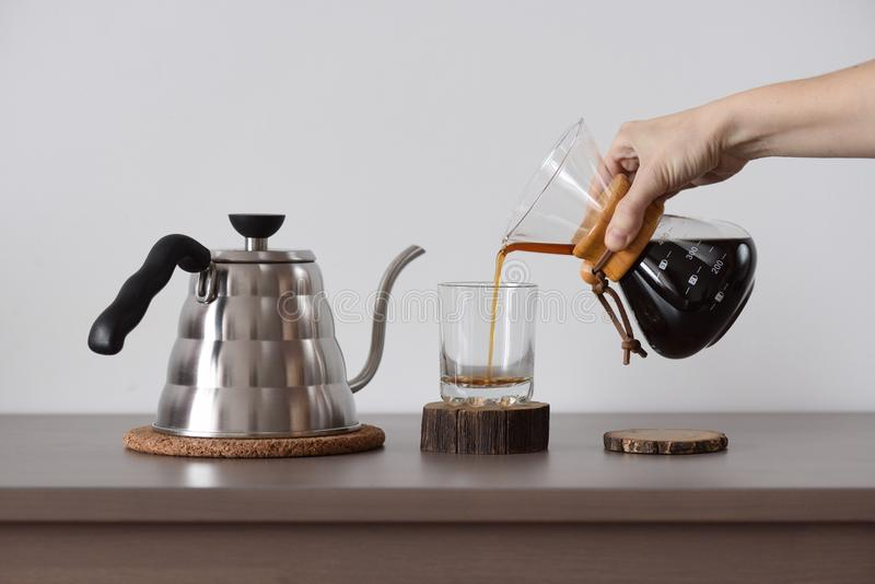 酿造的咖啡手中滴水咖啡壶 妇女手倒咖啡 免版税库存照片