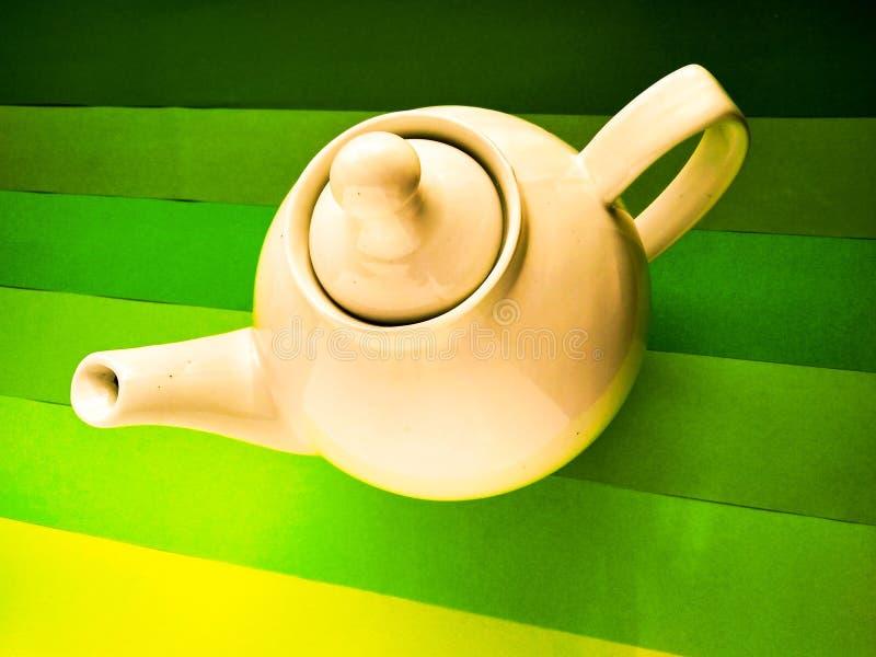 酿造的白色茶壶在绿色背景 库存图片