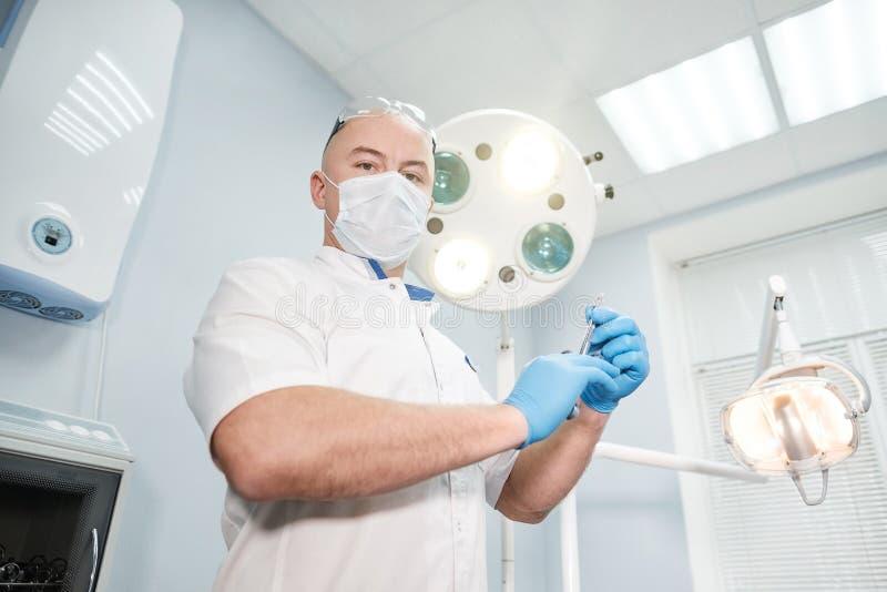 麻醉师医生在他的手上拿着一个注射器并且调查框架 图库摄影