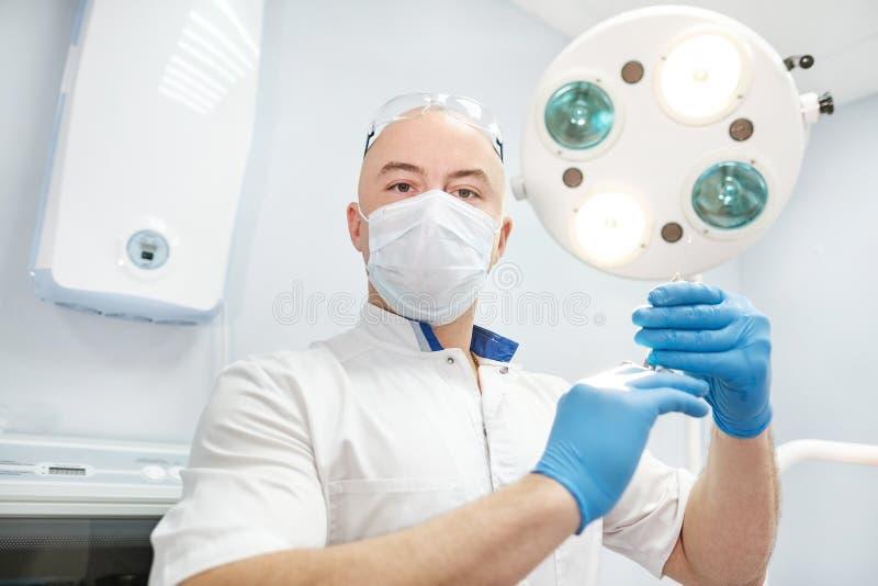麻醉师医生在他的手上拿着一个注射器并且调查框架 免版税库存图片