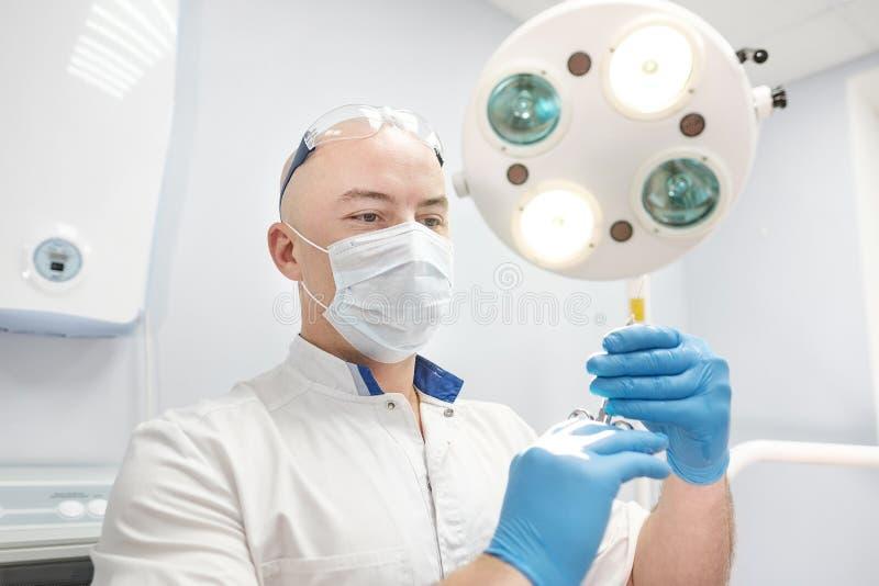 麻醉师医生在他的手上拿着一个注射器并且调查框架 库存图片