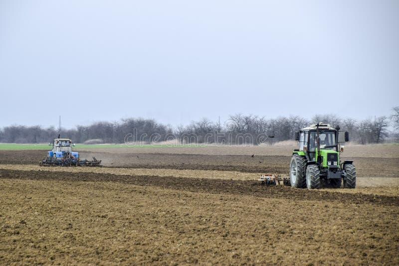 醉汉和在播种前松开在领域的土壤 拖拉机犁与犁的一个领域 图库摄影