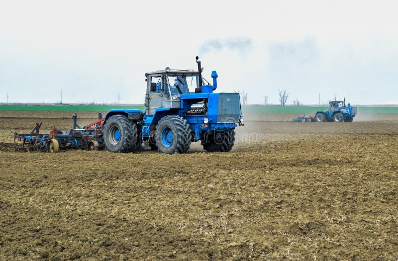 醉汉和在播种前松开在领域的土壤 拖拉机犁与a的一个领域 库存照片