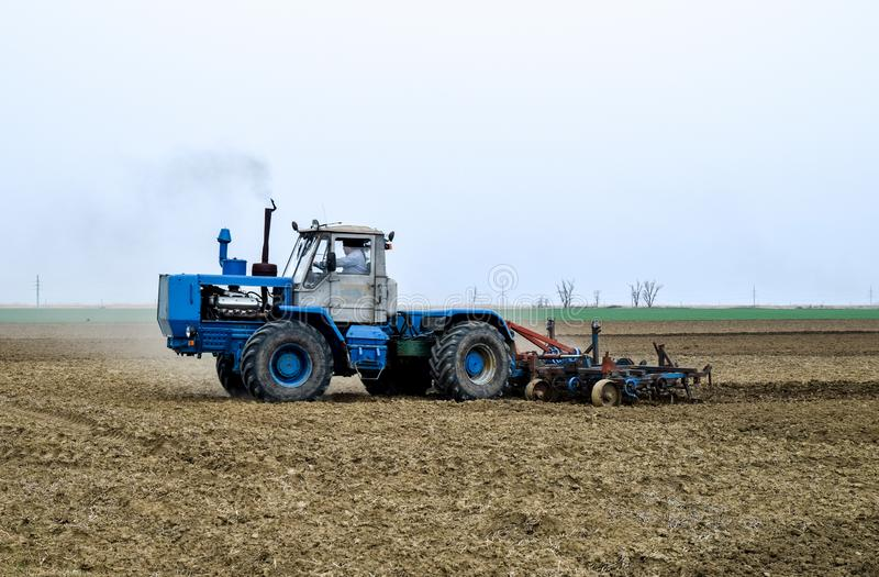 醉汉和在播种前松开在领域的土壤 拖拉机犁与a的一个领域 免版税图库摄影