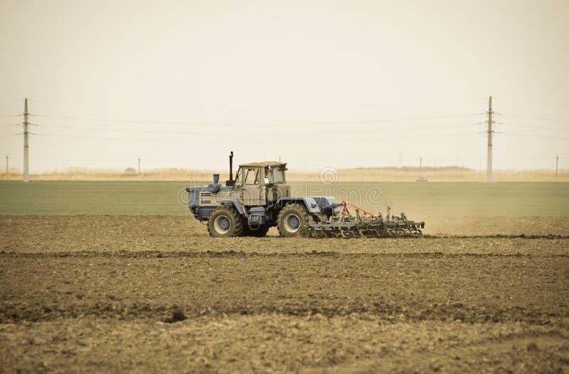 醉汉和在播种前松开在领域的土壤 拖拉机犁与a的一个领域 库存图片