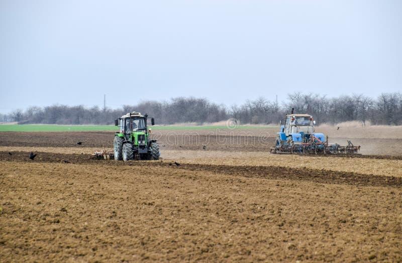 醉汉和在播种前松开在领域的土壤 拖拉机犁与a的一个领域 免版税库存图片