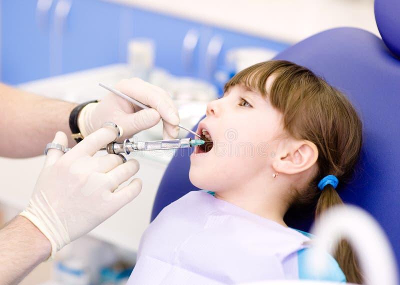 麻醉的接近的牙科医生他的藏品嘴开张耐心的注射器 免版税图库摄影
