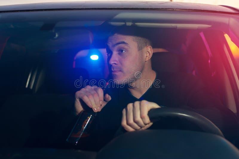 醉酒的司机由警察追逐了,当驾驶汽车时 免版税库存照片