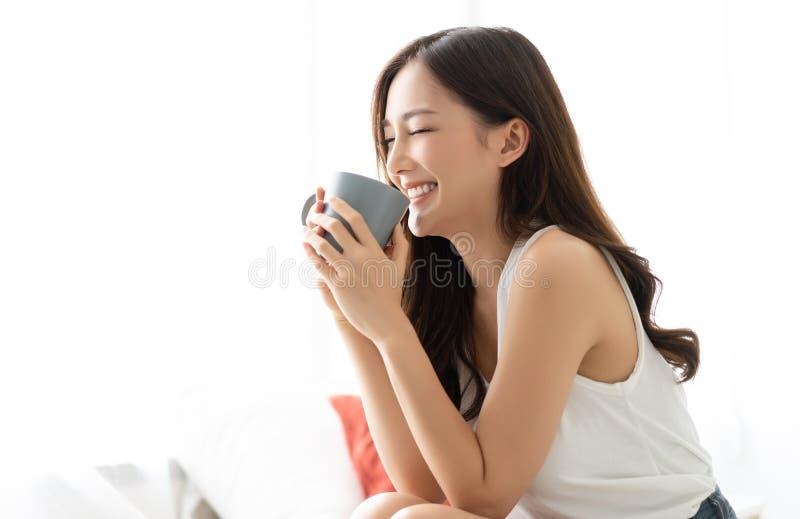 醒与咖啡的愉快的微笑的美丽的亚裔妇女在有闭上的眼睛的卧室 人生活方式概念 库存图片
