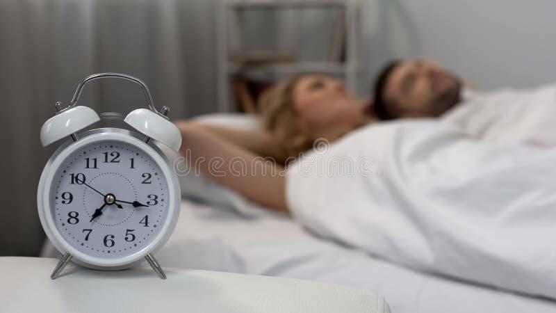 醒与闹钟的愉快的夫妇在早晨,在床上,家庭生活 免版税库存照片