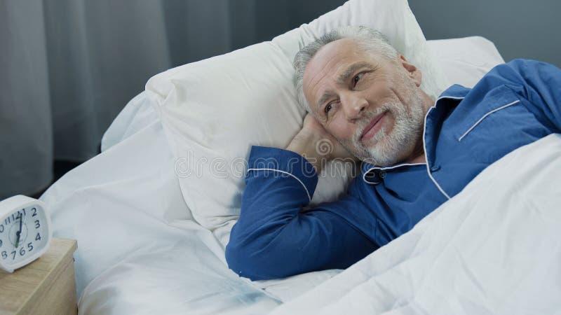 醒和微笑在舒适的健康睡眠,医疗保健以后的资深男性 库存照片