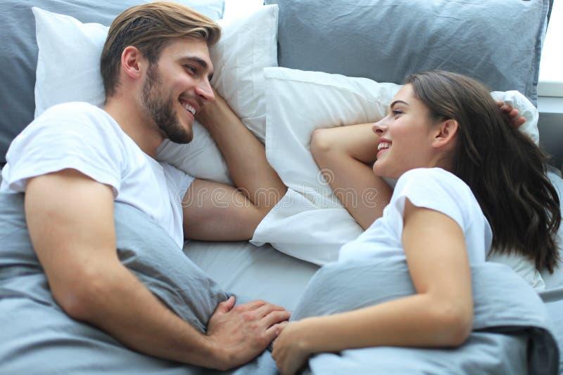 醒和看彼此的快乐的夫妇在床上 图库摄影