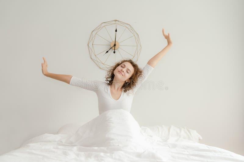 醒和舒展在她的床上的美丽的年轻女人早晨 免版税库存照片