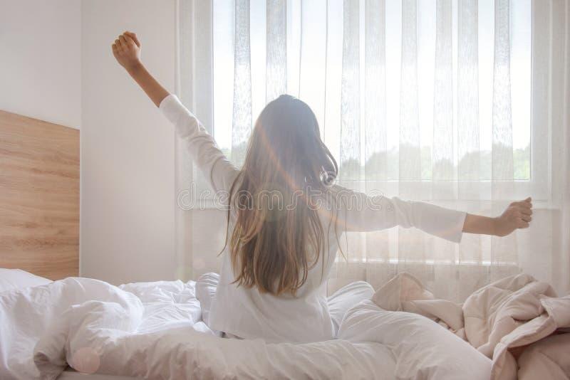 醒在她的卧室的年轻女人,坐舒展胳膊的床由窗口 免版税库存图片