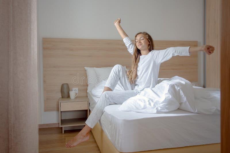 醒在她的卧室的年轻女人,坐舒展胳膊的床 免版税库存图片