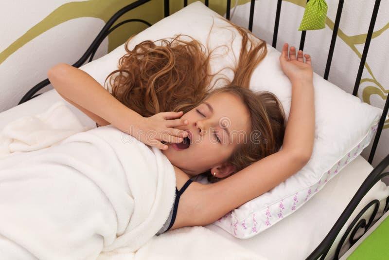 醒在她的床上的女孩 免版税库存图片