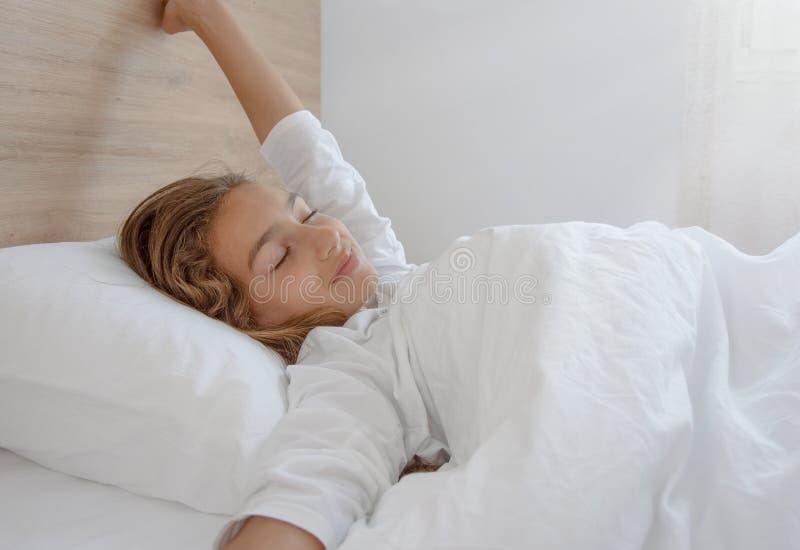 醒在好睡觉以后的愉快的妇女 库存图片