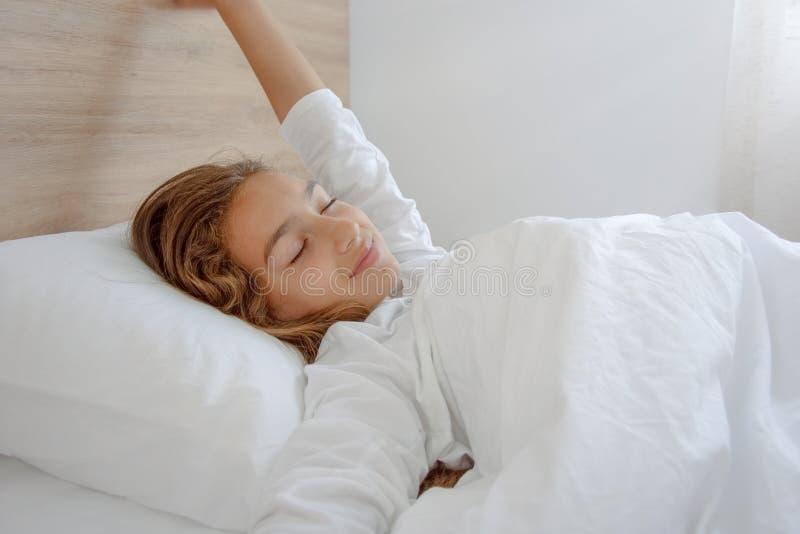 醒在好睡觉以后的愉快的妇女 免版税库存照片