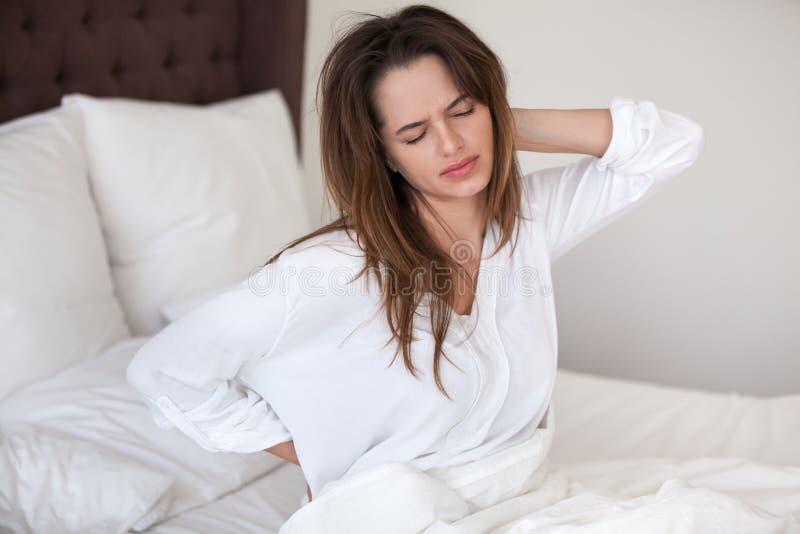 醒在床感觉脖子背部疼痛中的不快乐的妇女 免版税图库摄影