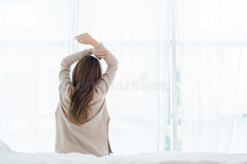 醒在早晨的后面观点的愉快的美丽的年轻亚裔妇女看通过窗口 图库摄影