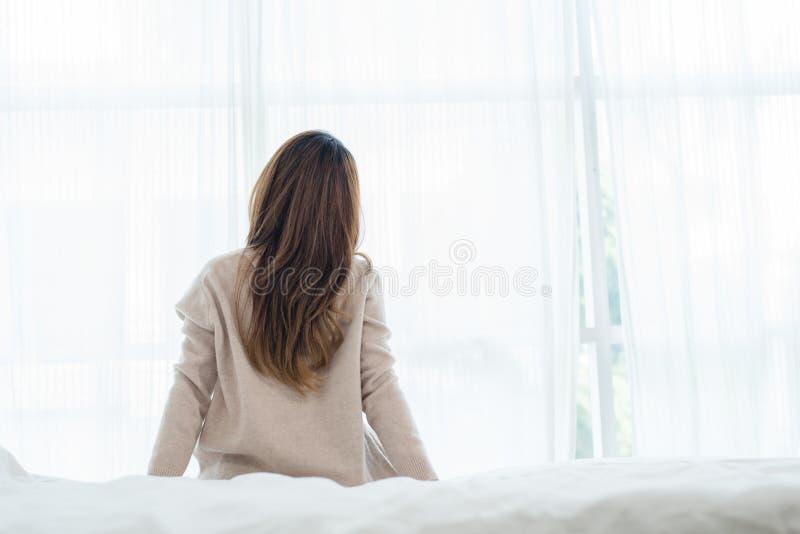 醒在早晨的后面观点的愉快的美丽的年轻亚裔妇女,坐床,舒展在舒适卧室 免版税库存图片