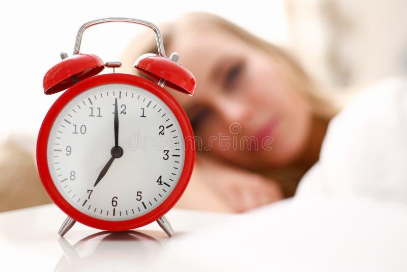 醒在早晨警报的年轻美丽的妇女 库存照片