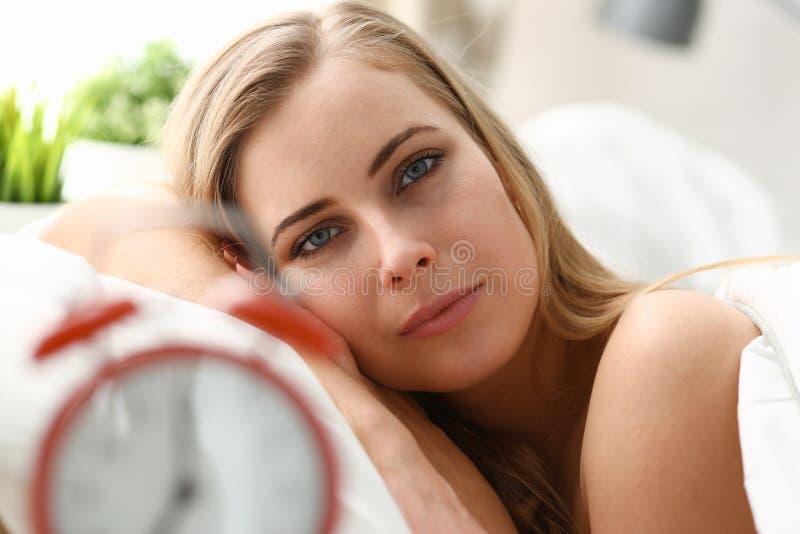 醒在早晨警报的年轻美丽的妇女 图库摄影