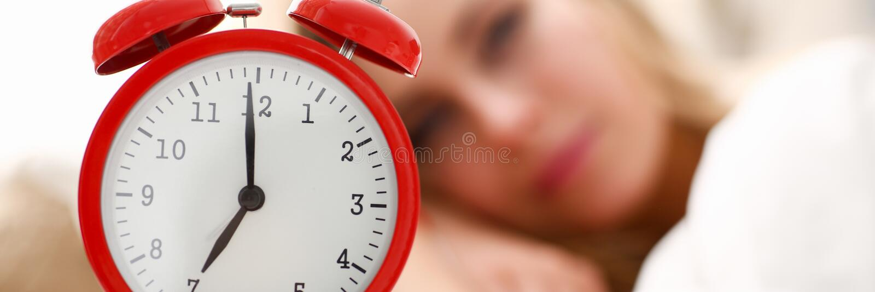 醒在早晨警报的年轻美丽的妇女 免版税库存图片