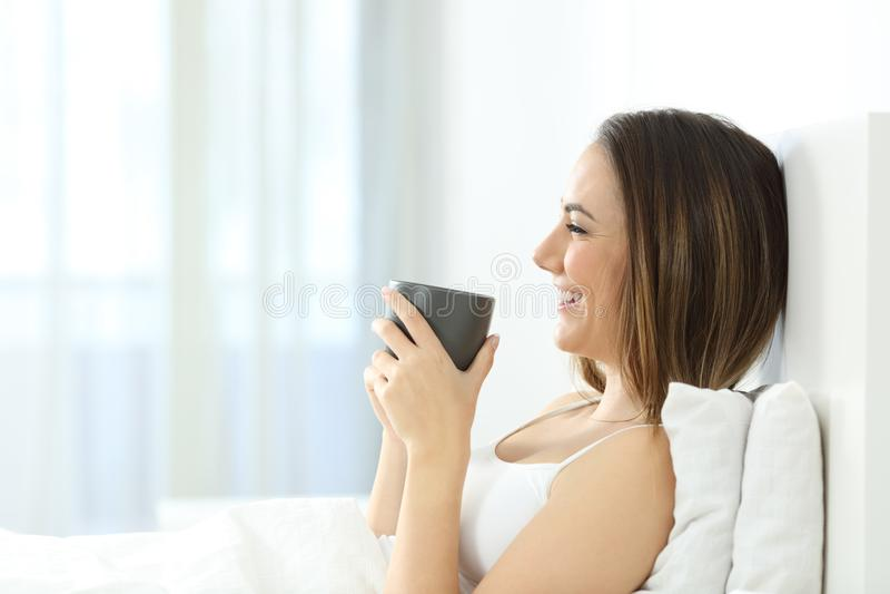 醒愉快的女孩食用在床上的早餐 库存图片