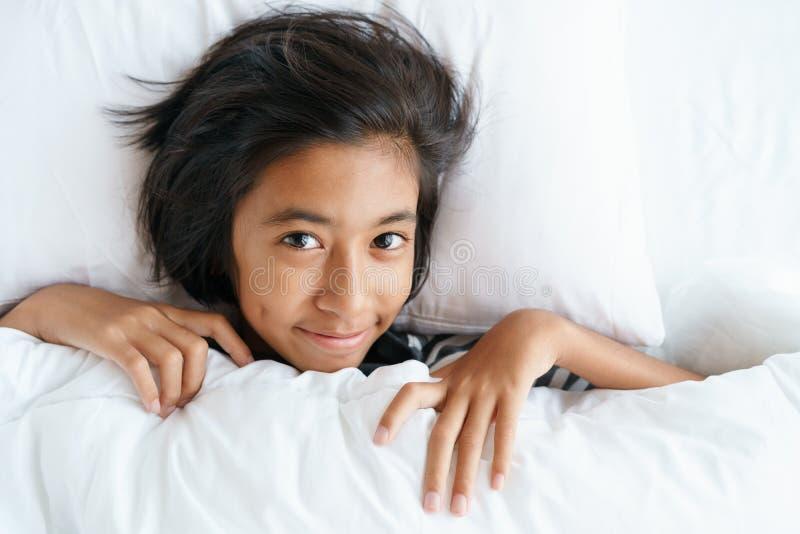 醒来从睡眠的亚裔逗人喜爱的女孩早晨 女孩的面孔是放松以后醒 库存照片
