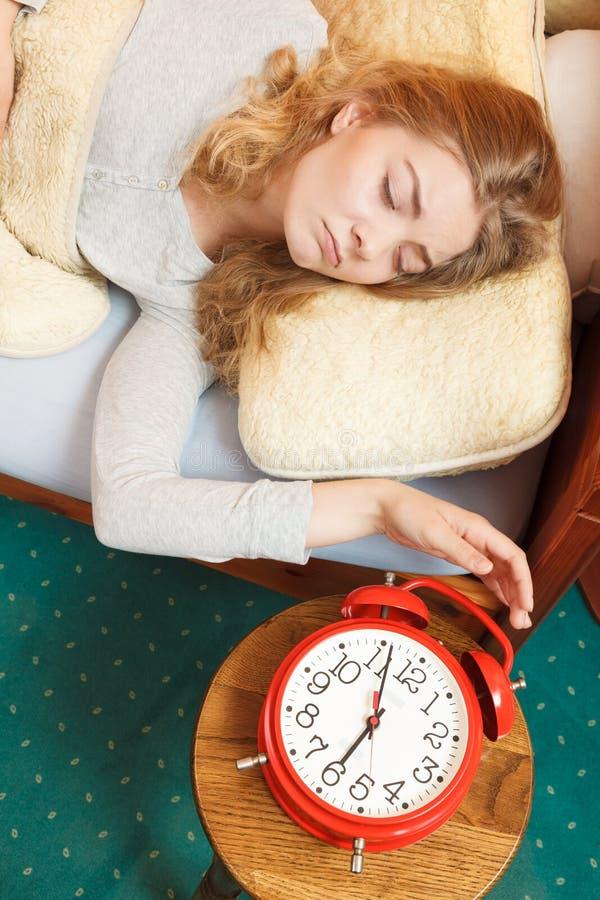 醒的妇女关闭闹钟在早晨 库存照片