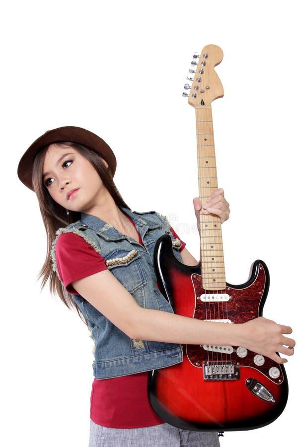 醒目摇摆物的夫人冷却与她的吉他的姿势,在白色bac 免版税库存照片