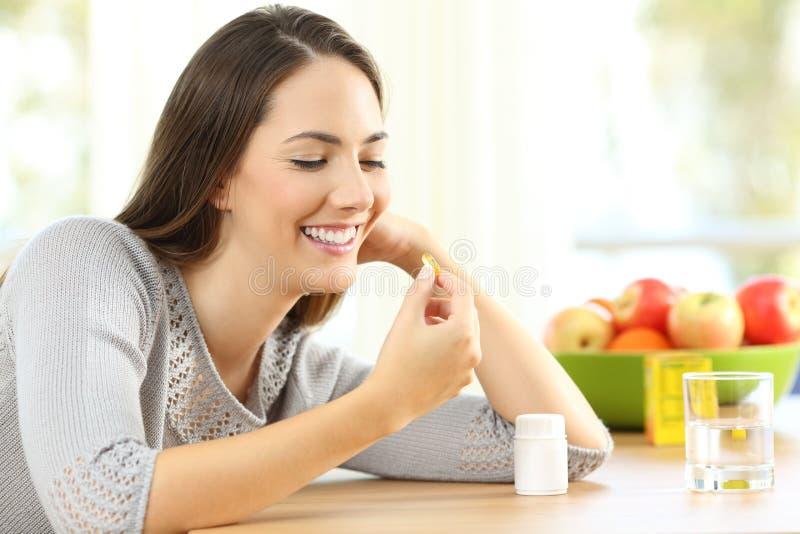 采取Ω 3个维生素药片的妇女 库存图片
