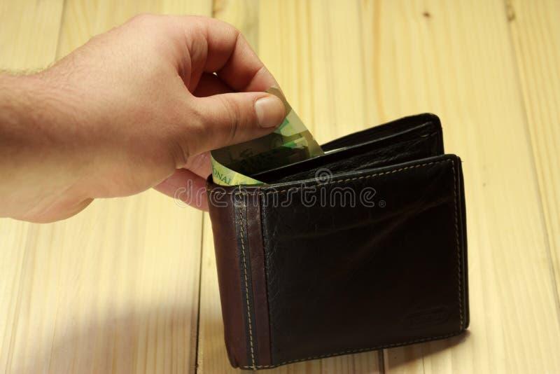 采取一些钱的手在钱包外面 库存照片