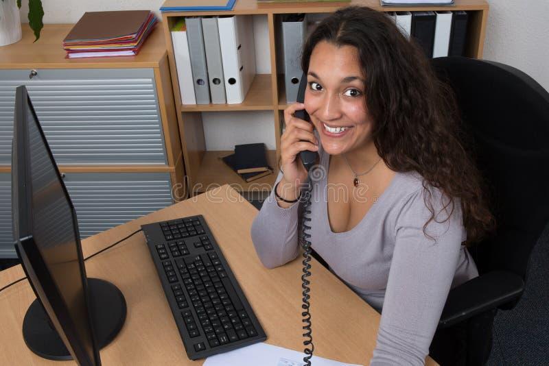 采取一次电话的女商人在办公室 库存图片