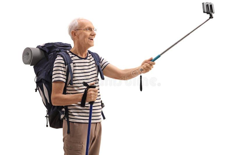 采取一selfie用棍子的年长男性远足者 库存图片