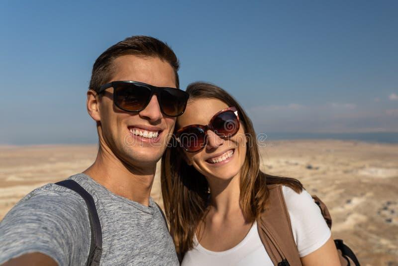 采取一selfie的年轻夫妇在以色列的沙漠 免版税图库摄影