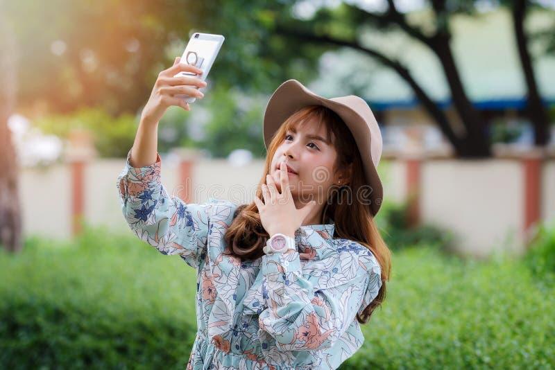 采取一selfie的葡萄酒礼服的俏丽的亚裔女孩在公园 免版税图库摄影