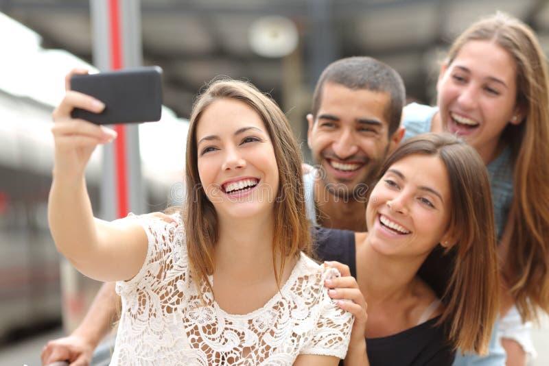 采取与一个巧妙的电话的小组四个朋友selfie 免版税库存照片