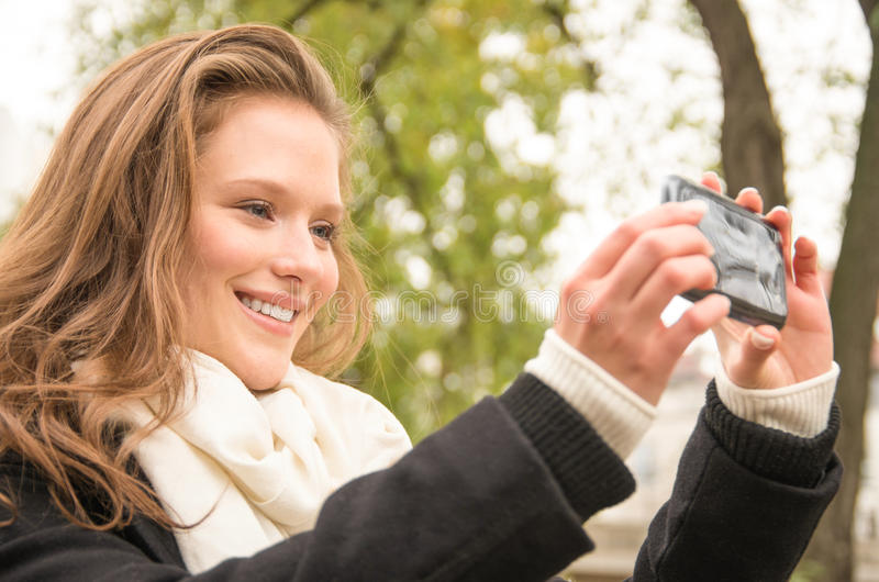 采取与一个现代电话的美丽的愉快的少妇一selfie 免版税库存图片
