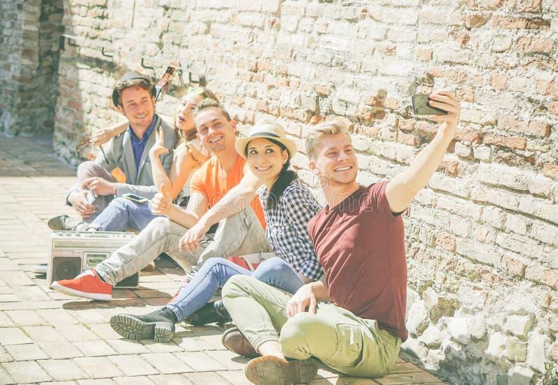 采取与一台流动智能手机照相机的小组多种族朋友一selfie -愉快的人自画象  图库摄影