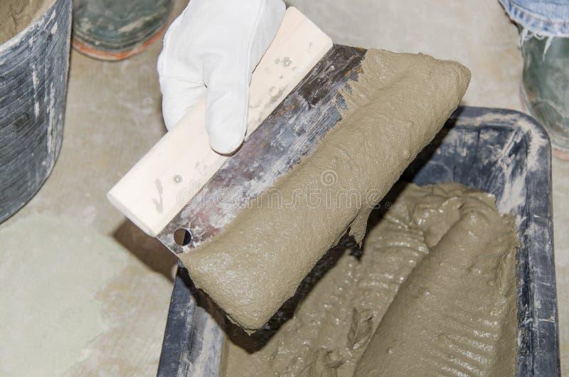 采取与一把被刻凹痕的修平刀的铺磁砖工瓦片胶粘剂 图库摄影