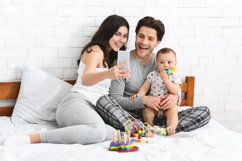 采取与他们可爱的婴孩的年轻父母selfie 免版税图库摄影