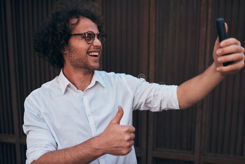 采取与他的智能手机的年轻英俊的商人自画象户外 愉快的微笑的男性佩带的白色衬衫和回合 库存照片