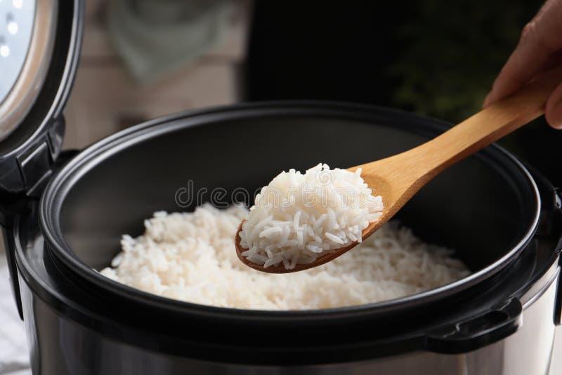 采取与匙子的妇女鲜美米从烹饪器材在厨房里 免版税库存图片