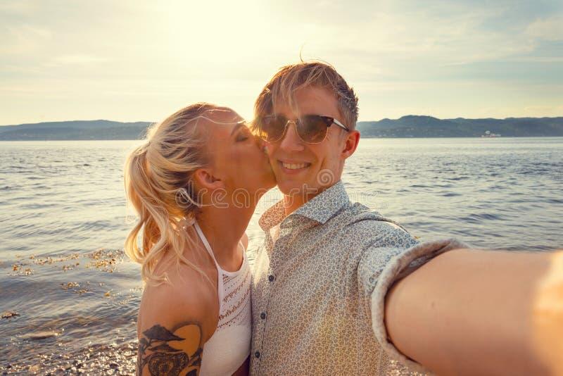 采取与女朋友的微笑的年轻人Selfie在海滩 库存图片