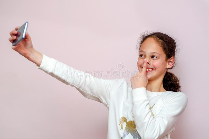 采取与她的手机的少年女孩selfie在桃红色背景 图库摄影