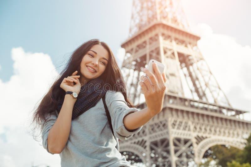 采取与她的手机的美丽的女孩滑稽的selfie在埃佛尔铁塔附近 免版税库存照片