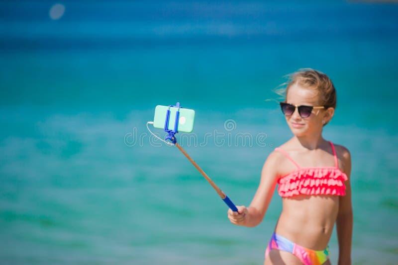采取与她的智能手机的小女孩selfie画象在海滩 可爱的式样制造的自画象背景 免版税库存照片
